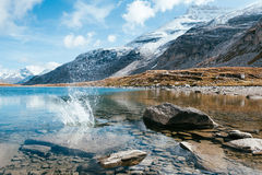 有石头和飞溅声的一个透明山湖 免版税库存照片