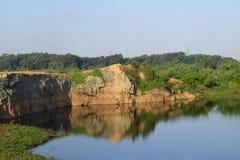 有石头的岩石湖和植物在水反射 免版税图库摄影