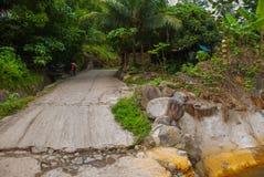 有石头的残破的混凝土路和一辆摩托车在夏天 菲律宾 巴伦西亚,海岛内格罗斯岛 图库摄影