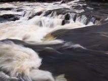 有石头的狂放的河,泡沫 图库摄影