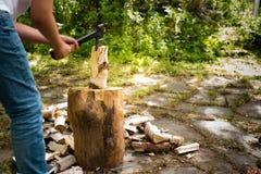 有砍在一块斩肉板的轴的年轻人木头 库存照片