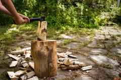 有砍在一块斩肉板的轴的年轻人木头 免版税图库摄影