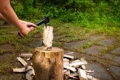 有砍在一块斩肉板的轴的年轻人木头 库存图片