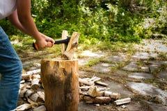 有砍在一块斩肉板的轴的年轻人木头 免版税库存照片