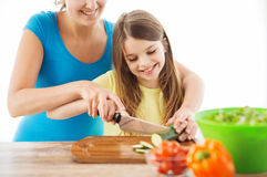有砍黄瓜的母亲的微笑的小女孩 免版税库存图片