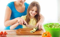 有砍黄瓜的母亲的微笑的小女孩 免版税库存照片