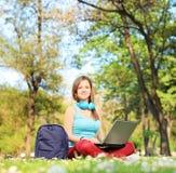 有研究一台膝上型计算机的耳机的女学生在公园 库存照片