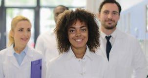有研究员队的年轻非裔美国人的科学家女孩现代实验室愉快的微笑的不同的男人和妇女的 股票视频