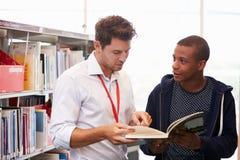 有研究的老师帮助的大学生在图书馆里 免版税库存照片