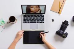 有研究膝上型计算机的照相机的妇女在桌上 库存照片