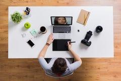 有研究膝上型计算机的照相机的妇女在桌上 库存图片