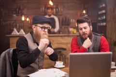 有研究计算机的时髦的胡子的年轻人在葡萄酒客栈 免版税库存图片