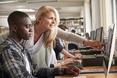 有研究计算机的男学生的老师在大学图书馆里 免版税图库摄影