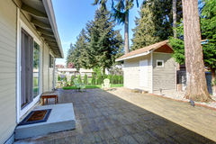 有砖地和两把绿色椅子的后院甲板 小棚子看法  免版税库存图片