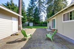 有砖地和两把绿色椅子的后院甲板 图库摄影