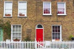 有砖墙、红色门和白色篱芭的伦敦典型的房子 库存图片