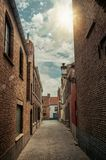 有砖墙和阳光的狭窄的胡同在布鲁日的市中心 库存图片