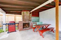 有砖壁炉和家具的外部被盖的露台 免版税库存图片
