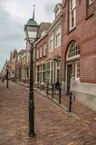 有砖房子的空的街道和灯在一多云天在海特勒伊登贝赫 免版税库存图片