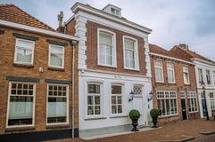 有砖房子的街道在多云天在海特勒伊登贝赫村庄  免版税库存照片