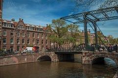 有砖瓦房、开启桥、自行车和蓝天的运河在阿姆斯特丹 免版税库存照片