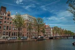 有砖瓦房、桥梁和晴朗的蓝天的沿途有树的运河在阿姆斯特丹 库存照片