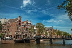 有砖瓦房、自行车在桥梁和晴朗的蓝天的运河在阿姆斯特丹 免版税库存照片