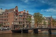 有砖瓦房、自行车在桥梁和晴朗的蓝天的运河在阿姆斯特丹 免版税图库摄影
