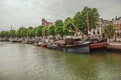 有砖瓦房的宽沿途有树的运河在它旁边的一条街道和被停泊的小船在多德雷赫特的一多云天 免版税库存照片