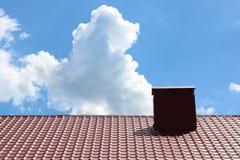 有砖的红色金属房子瓦顶房顶烟囱反对蓝天背景 库存图片