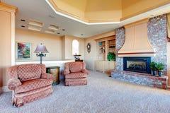 有砖背景壁炉的丰富的家庭娱乐室 库存图片