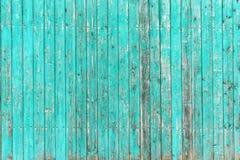 有破裂的油漆绿宝石纹理的木篱芭  图库摄影