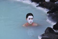 有硅土泥面具的地热温泉访客在著名蓝色盐水湖放松并且刷新 免版税库存图片