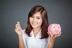 有硬币和桃红色猪钱箱的美丽的亚裔女孩 库存图片
