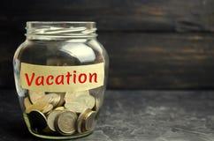 有硬币和题字的'假期'玻璃瓶子 财政预算计划 货币积累休息和手段的 Famil 库存照片