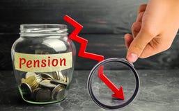 有硬币和题字的'退休金'和和下来箭头玻璃瓶子 衰落/减少退休金付款 退休 财务 免版税库存照片