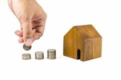 有硬币概念的木玩具房子 库存照片