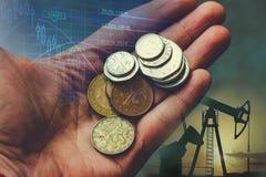 有硬币的手在石油生产背景  企业概念,自然资源的提取 免版税库存照片