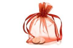 有硬币的红色礼物大袋 免版税库存图片