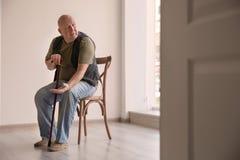 有硬币的老人坐椅子在空的屋子里 免版税库存照片
