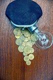 有硬币的老皮革钱包和在桌上的一个电灯泡 库存照片