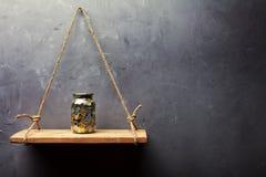 有硬币的玻璃瓶子在老木架子 库存照片