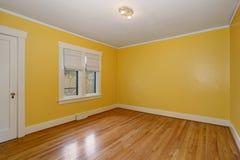 有硬木地板和双重窗口的黄色空的室 库存照片