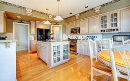 有硬木地板和绿色墙壁的大美丽的空白厨房。 免版税库存照片