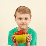 有碗的小男孩新鲜的草莓 免版税库存照片