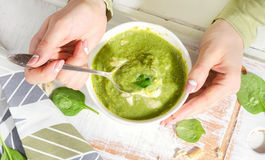 有碗的少妇手绿色spinash汤 免版税库存照片