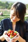 有碗的微笑女孩草莓 免版税库存图片