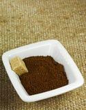 有碾碎的咖啡和红糖立方体的陶瓷碗在纹理袋装背景 图库摄影