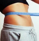 有磁带的妇女测量的腰部在结喜欢礼物,非洲人棕褐色 库存图片