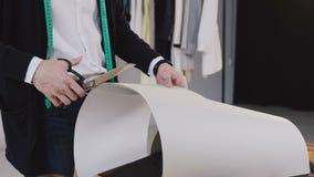有磁带线路的年轻男性设计师在他的站立在女装裁制业演播室和裁减的脖子与剪刀一个样式新的 影视素材